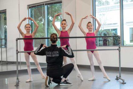 Dance teacher instruction three young ballerinas