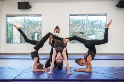 Dance teacher with three teens on mat